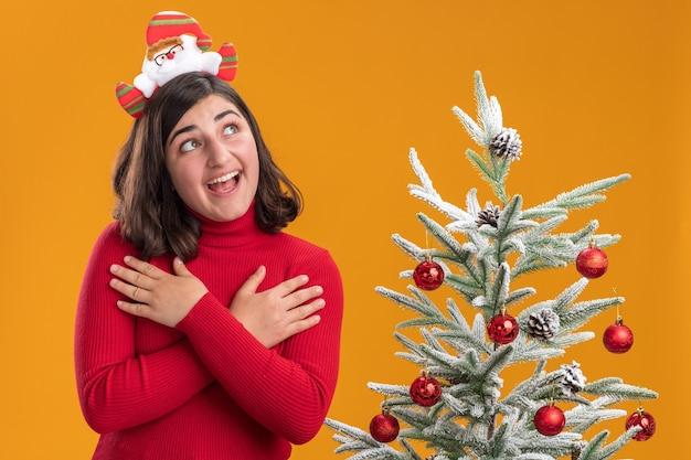 Junges mädchen im weihnachtspullover, der lustiges stirnband neben einem weihnachtsbaum über orange hintergrund trägt