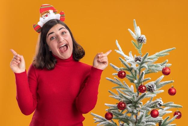 Junges mädchen im weihnachtspullover, der lustiges stirnband trägt, das kamera glücklich und aufgeregt neben einem weihnachtsbaum über orange hintergrund betrachtet
