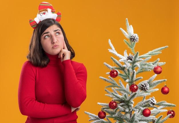Junges mädchen im weihnachtspullover, der lustiges stirnband trägt, das verwirrt neben einem weihnachtsbaum über orange hintergrund schaut