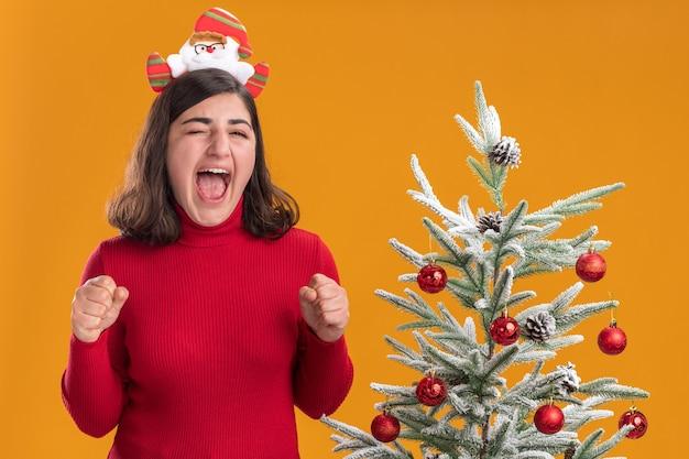 Junges mädchen im weihnachtspullover, der lustiges und aufgeregtes lustiges stirnband neben einem weihnachtsbaum über orange hintergrund trägt
