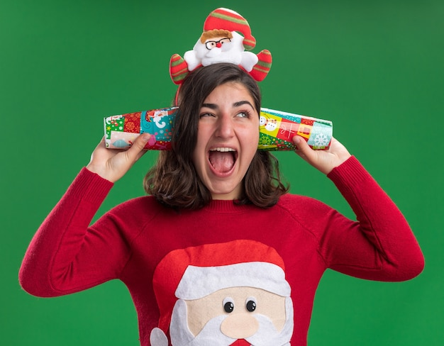 Junges mädchen im weihnachtspullover, der weihnachtsmannmütze hält bunte pappbecher nahe ihren ohren glücklich und aufgeregt steht über grüner wand