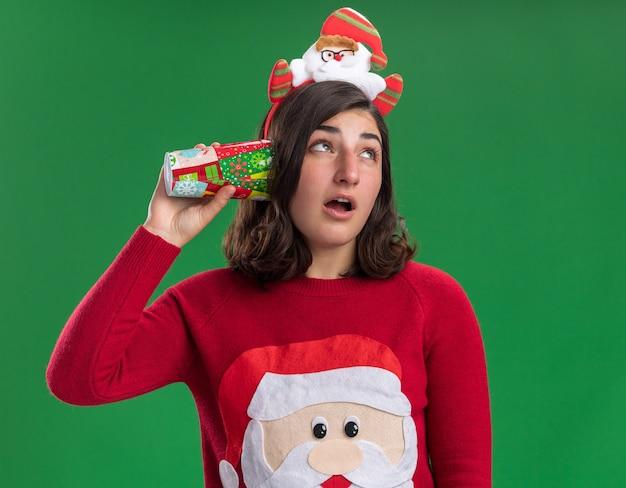 Junges mädchen im weihnachtspullover, der weihnachtsmütze trägt, die bunten pappbecher über ihrem ohr hält, der versucht, etwas zu hören, das über grüner wand steht