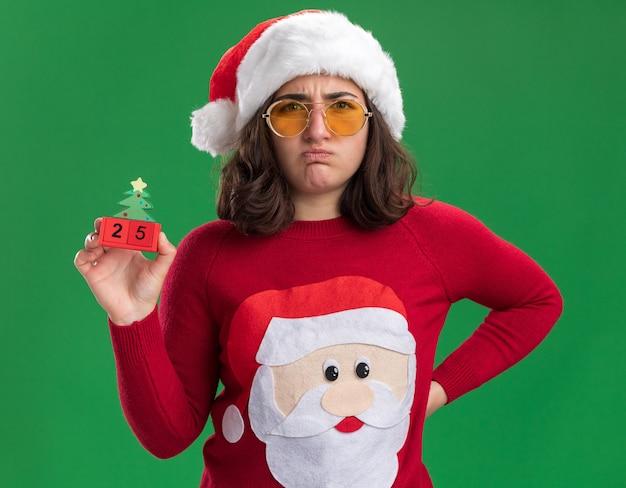 Junges mädchen im weihnachtspullover, der weihnachtsmütze und brille hält, die spielzeugwürfel mit nummer 25 unzufrieden hält, spitzen lippen, die über grüner wand stehen