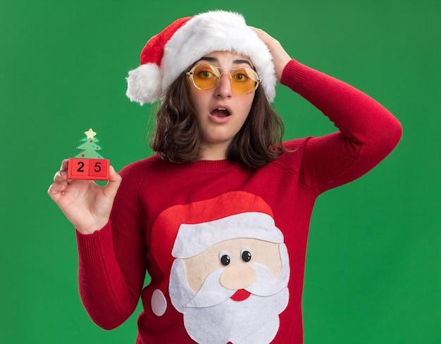 Junges mädchen im weihnachtspullover, der weihnachtsmütze und brille hält, die spielzeugwürfel mit nummer fünfundzwanzig überrascht und erstaunt über grüner wand stehen