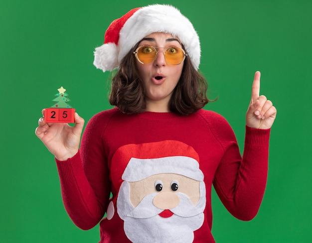 Junges mädchen im weihnachtspullover, der weihnachtsmütze und brille hält, die spielzeugwürfel mit nummer fünfundzwanzig überrascht zeigt zeigefinger, der neue idee über grüner wand steht