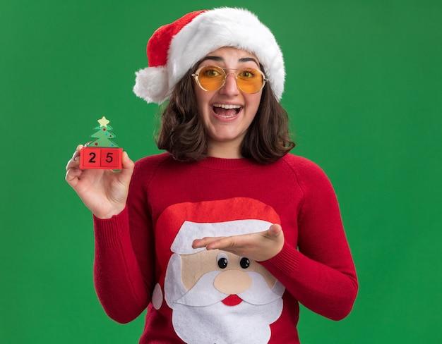 Junges mädchen im weihnachtspullover, der weihnachtsmütze und gläser hält, die spielzeugwürfel mit nummer fünfundzwanzig lächelnd fröhlich präsentieren mit arm stehen über grüner wand tragen