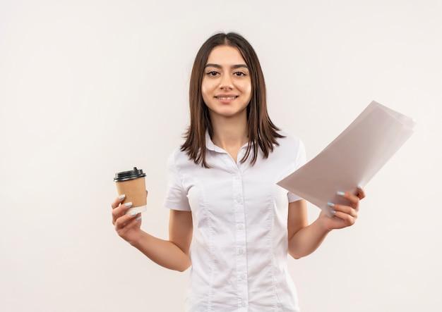 Junges mädchen im weißen hemd, das kaffeetasse und leere seiten hält, die zuversichtlich über weißer wand stehen