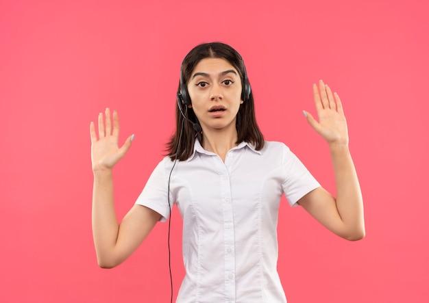 Junges mädchen im weißen hemd und in den kopfhörern, die handflächen in der übergabe anhebend und überrascht stehen über rosa wand heben