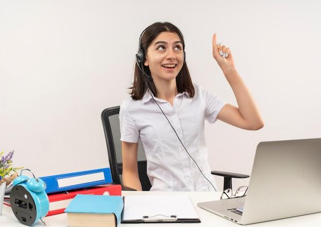 Junges mädchen im weißen hemd und in den kopfhörern, die mit zeigefinger nach oben zeigen, die große idee haben, am tisch mit ordnern und laptop über weißer wand zu sitzen