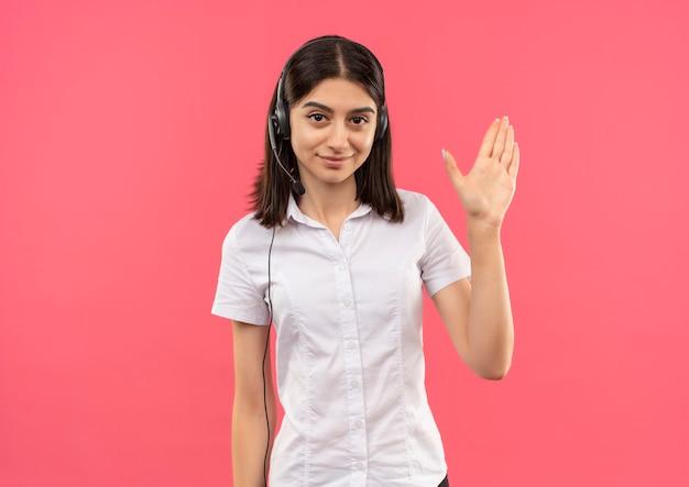 Junges mädchen im weißen hemd und in den kopfhörern, die nach vorne lächelnd freundlich winkend mit der hand stehen über rosa wand schauen