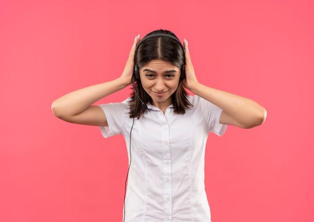 Junges mädchen im weißen hemd und in den kopfhörern, die ohren mit den händen mit genervtem ausdruck schließen, die über rosa wand stehen