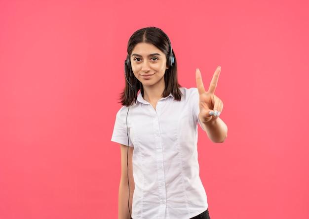 Junges mädchen im weißen hemd und in den kopfhörern, zeigend und zeigend mit den fingern oben nummer zwei lächelnd stehend über rosa wand