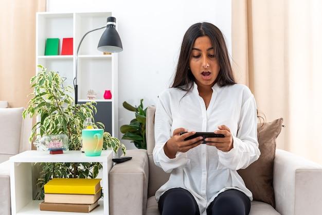 Junges mädchen im weißen hemd und in der schwarzen hose, die spiele mit ihrem smartphone spielen, das überrascht sitzt, das auf dem stuhl im hellen wohnzimmer sitzt