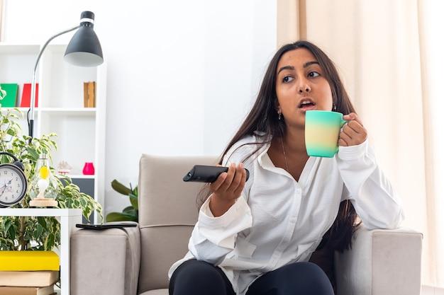 Junges mädchen im weißen hemd und in der schwarzen hose mit tv-fernbedienungs-haltebecher, der fernsehen sitzt auf dem stuhl im hellen wohnzimmer sitzt
