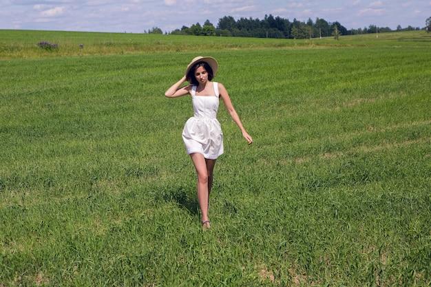 Junges mädchen im weißen kleid und mit einem strohhut ist auf der grünen wiese mit gras und lächeln, sommer. das modell geht vor der kamera