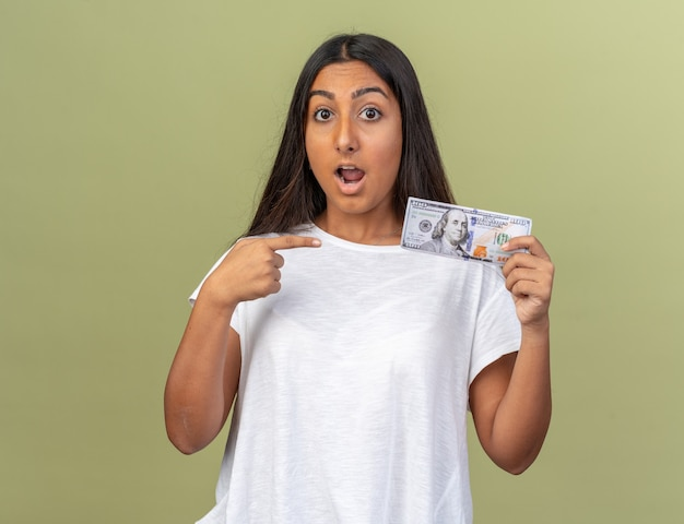 Junges mädchen im weißen t-shirt, das bargeld hält und mit dem zeigefinger auf geld zeigt, das erstaunt und überrascht aussieht looking