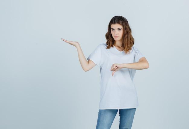 Junges mädchen im weißen t-shirt, das die einladende geste mit dem daumen nach unten zeigt und zögernd, vorderansicht schaut.