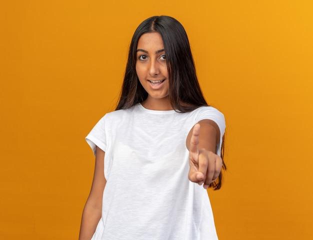 Junges mädchen im weißen t-shirt, das die kamera anschaut und fröhlich mit dem zeigefinger auf die kamera zeigt, die über orangefarbenem hintergrund steht