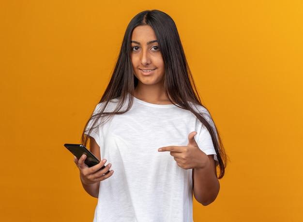 Junges mädchen im weißen t-shirt, das ein smartphone hält und mit dem zeigefinger darauf zeigt, lächelt selbstbewusst über orange
