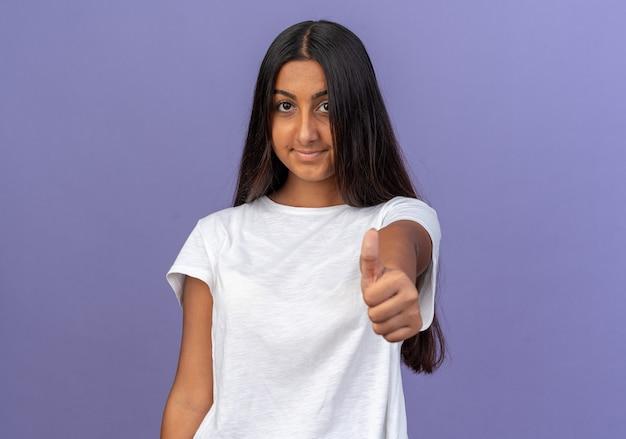 Junges mädchen im weißen t-shirt, das in die kamera schaut und selbstbewusst lächelt und daumen nach oben über blau zeigt