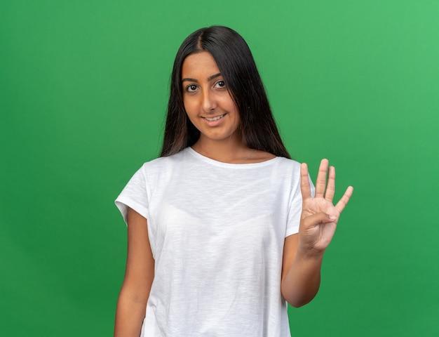 Junges mädchen im weißen t-shirt, das lächelnd in die kamera schaut und mit den fingern nummer vier nach oben zeigt
