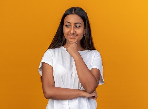 Junges mädchen im weißen t-shirt, das mit der hand auf ihrem kinn beiseite schaut und lächelt, das über orangefarbenem hintergrund steht