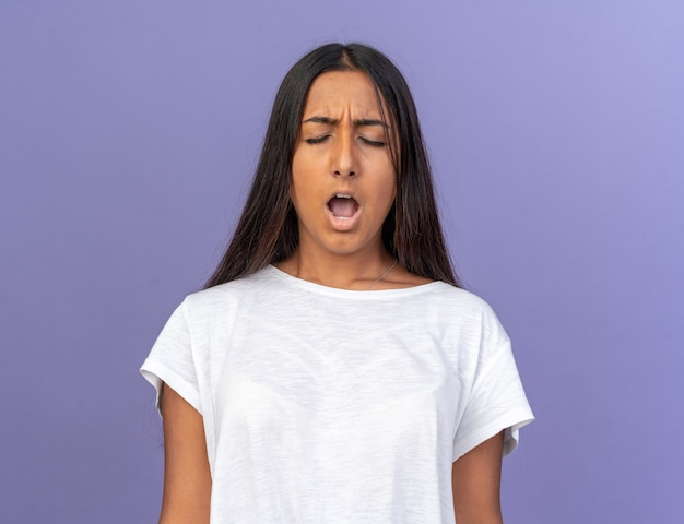 Junges mädchen im weißen t-shirt, das mit frustriertem ausdruck schreit