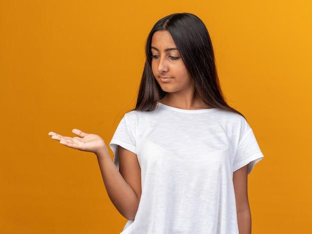 Junges mädchen im weißen t-shirt, das mit selbstbewusstem ausdruck beiseite schaut und kopienraum mit dem arm ihrer hand über orangefarbenem hintergrund präsentiert