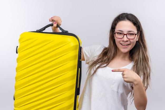 Junges mädchen im weißen t-shirt, das reisekoffer hält, der mit dem finger darauf zeigt, der fröhlich lächelt