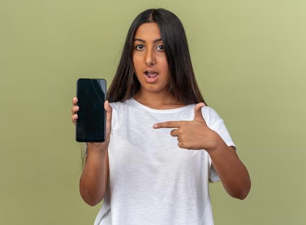 Junges mädchen im weißen t-shirt, das smartphone hält und mit dem zeigefinger darauf zeigt, dass es selbstbewusst auf grünem hintergrund steht