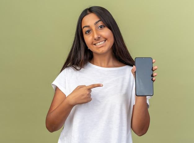 Junges mädchen im weißen t-shirt, das smartphone hält und mit dem zeigefinger darauf zeigt, fröhlich lächelnd