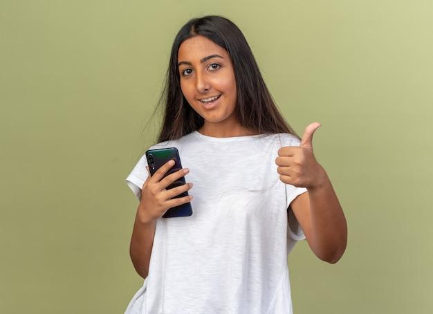 Junges mädchen im weißen t-shirt, das smartphone mit blick in die kamera hält und mit glücklichem gesicht lächelt