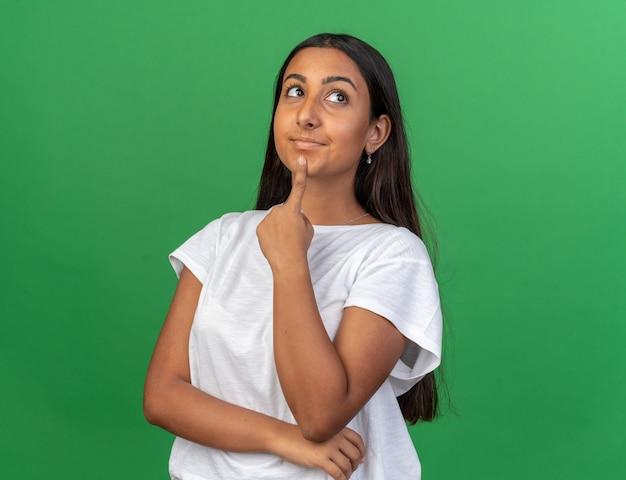 Junges mädchen im weißen t-shirt, das verwirrt auf grünem hintergrund steht