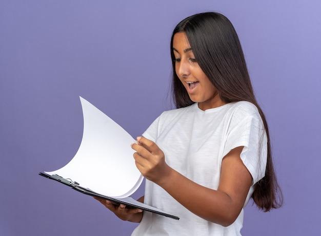 Junges mädchen im weißen t-shirt, das zwischenablage mit leeren seiten hält und es mit einem lächeln auf einem glücklichen gesicht auf blauem hintergrund betrachtet