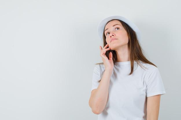 Junges mädchen im weißen t-shirt, hut, der ihre gesichtshaut auf wange berührt und verträumte vorderansicht schaut.