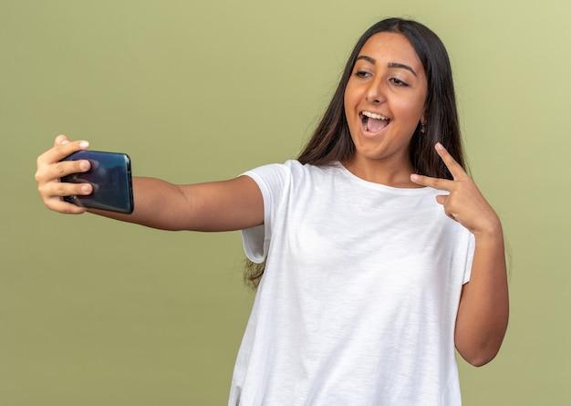 Junges mädchen im weißen t-shirt macht selfie mit smartphone lächelnd und zeigt ein v-zeichen auf grünem hintergrund