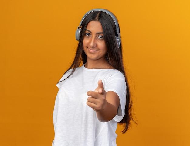 Junges mädchen im weißen t-shirt mit kopfhörern, das in die kamera schaut und fröhlich mit dem zeigefinger auf die kamera zeigt, die über orange steht
