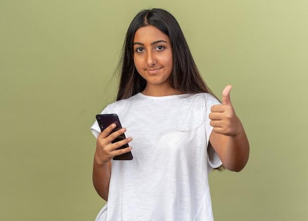 Junges mädchen im weißen t-shirt mit smartphone, das lächelnd in die kamera schaut und daumen hoch steht über grünem hintergrund