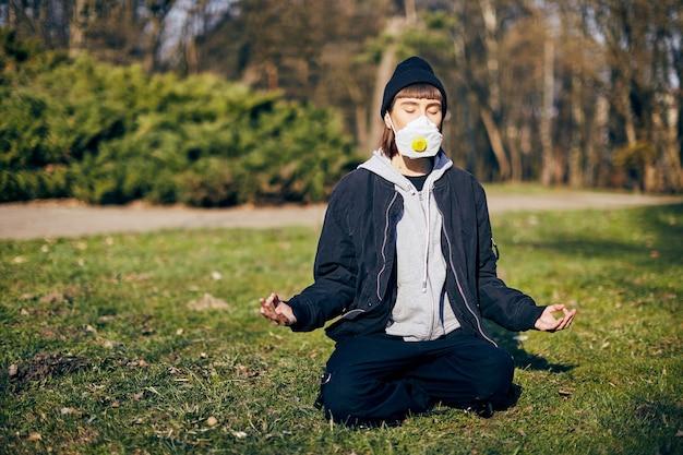 Junges mädchen in atemmaske meditiert im park mit geschlossenen augen, bleiben sie ruhig, während coronavirus-pandemie, atemübungen in der grünen zone während covid19, sichere meditation auf dem grünen gras