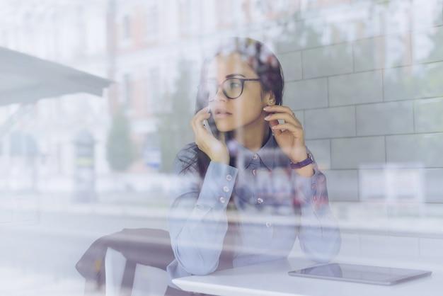 Junges mädchen in blauem hemd und brille telefoniert und sitzt in einem café