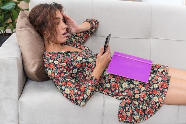 Junges mädchen in blumenkleid mit buch und smartphone, das verwirrt auf einer couch im hellen wohnzimmer liegt