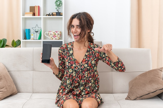 Junges mädchen in blumenkleid mit smartphone sieht glücklich und fröhlich aus