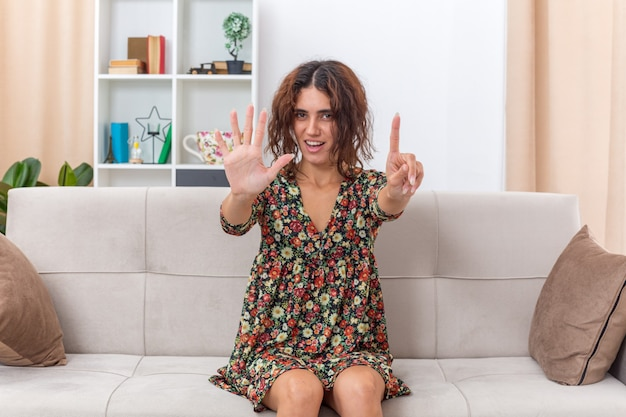 Junges mädchen in blumenkleid sieht glücklich und positiv aus und zeigt nummer fünf und zeigefinger lächelnd auf einer couch im hellen wohnzimmer sitzend