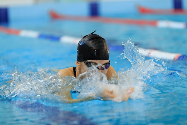 Junges mädchen in brille und mütze schwimmen schmetterlingsstil im blauen wasserpool.