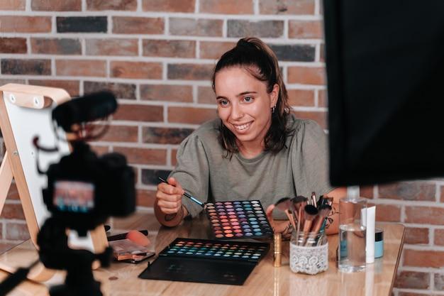 Junges mädchen in den zwanzigern beim schminken live für ihre make-up-anhänger