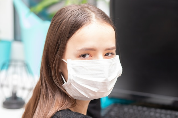 Junges mädchen in der antibakteriellen maske bei der arbeit im büro