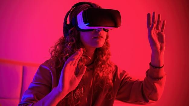 Junges mädchen in der brille der virtuellen realität mit blauer und roter beleuchtung im raum mit erhobenen händen. unterhaltung zu hause Premium Fotos