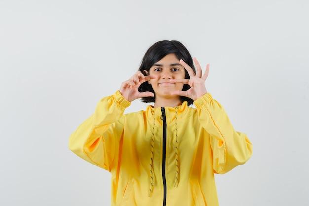 Junges mädchen in der gelben bomberjacke, die geometrische form mit händen zeigt und ernst schaut