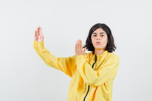 Junges mädchen in der gelben bomberjacke, die hände streckt, wie schuppen zeigt und ernst schaut