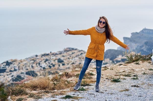 Junges mädchen in der gelben parkajacke panoramische berg- und seeansicht genießend